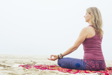 Mature woman performing gyan mudra while doing meditation on sand at beach