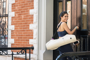 Smiling fit woman carrying bag while locking front door of house