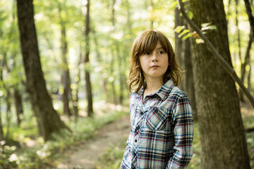 Thoughtful boy with brown hair looking away while standing in forest
