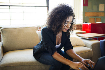 Beautiful young businesswoman using laptop while sitting on sofa in office