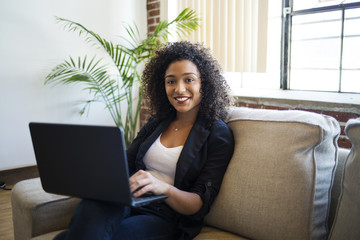 Portrait of smiling young businesswoman with laptop sitting on sofa in office