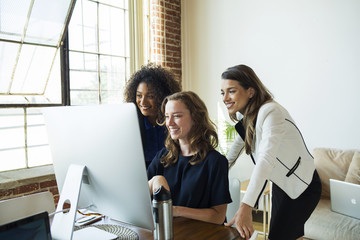 Smiling multiethnic businesswomen looking at computer monitor in office