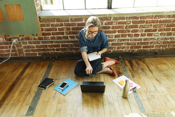 High angle view of businesswoman using laptop while sitting on hardwood floor in office