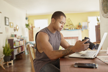 Young man with laptop holding camera while sitting at table at home