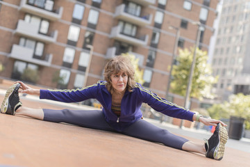 Full length of fit senior woman doing splits while touching toes in city