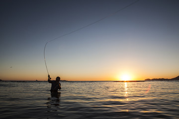 Man fishing while standing in river against clear sky during sunset