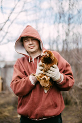 Concept of countryside life. Man holding a chicken