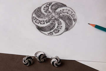 Beautiful diamond earrings and a ring with a picture on white paper. Luxury jewelry, close-up. Selective focus