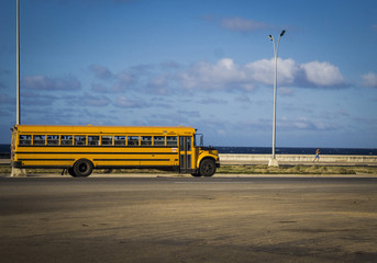 photograph of a very old school bus, from the 60s, crossing a highway that is next to the sea. Vintage concept