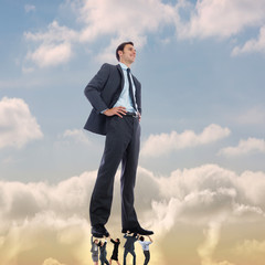 Business team supporting boss against beautiful blue sky with clouds