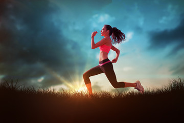 Full length of healthy woman jogging  against blue sky over grass