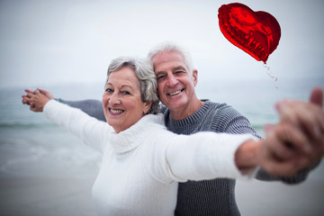 Red heart balloon against portrait of happy senior couple with arms outstretched 3d