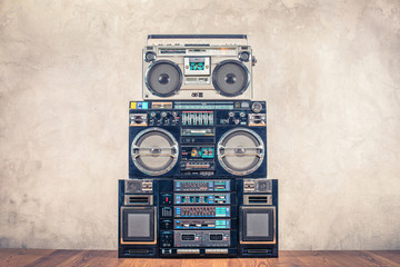 Retro design ghetto blaster stereo radio cassette tape recorders boombox tower from circa 80s front concrete wall background. Vintage instagram old style filtered photo