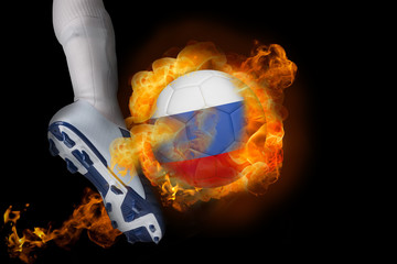 Football player kicking flaming russia ball against black