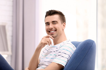 Young man sitting in armchair at home