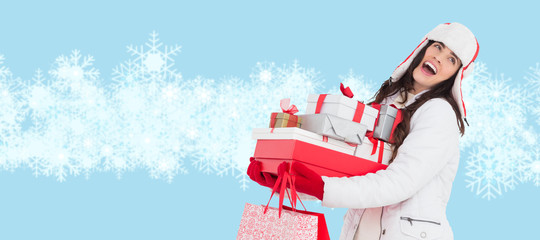 Brunette in winter clothes holding many gifts and shopping bags against snowflakes over blue background