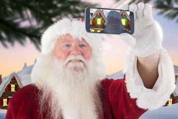 Santa taking a selfie on phone against cute christmas village with tree
