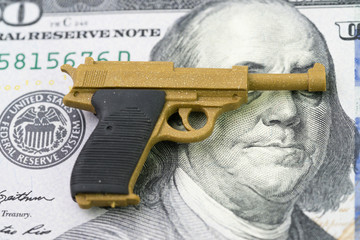 American firearm or gun business with big money concept, gun control policy in united state of America after many of mass shooting, miniature toy guns on Franklin eyes and face of US dollar banknote