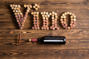 Vino lettering with bottle of wine on wood