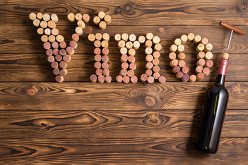 Vino lettering made of corks with bottle of wine