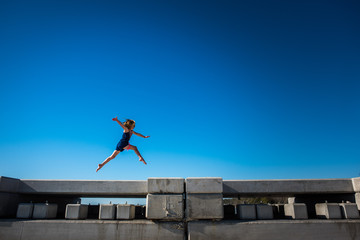 girl jumping in air with arms out wide with blue sky  at the beach
