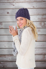 Pretty blonde in winter fashion holding mug against wooden planks