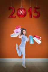 Smiling brunette jumping while holding shopping bags against room with wooden floor