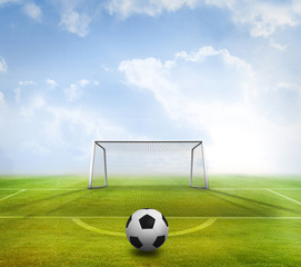 Black and white football against football pitch and goal under blue sky