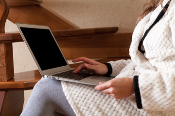 the girl in a dressing gown with the laptop stays at home on a ladder