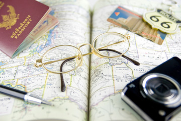 Eyeglasses, pen, passport book and camera on map