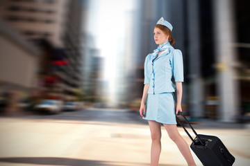 Pretty air hostess pulling suitcase against new york street