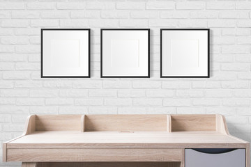 working table with blank photo frames in the empty studio with white brick wall.