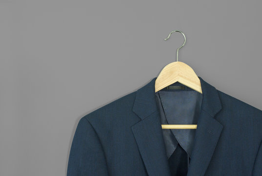 wood hanger with navy blue suit isolated on grey background