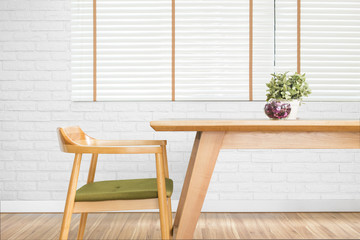 Dining table set with chair in the cozy dining room with white brick wall.