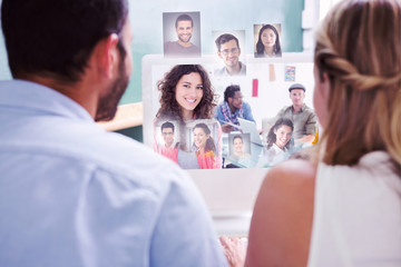 Colleagues looking at computer against smiling woman with creative team working behind