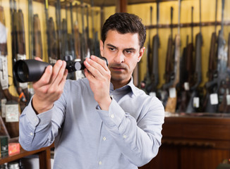 Male owner of hunting shop checking optical sights