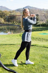 Young pretty female golf player looks successfully after the golf game