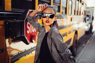 Beautiful fashionable Asian model girl wearing stylish black sunglasses posing outdoors on city street near bus
