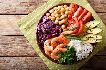 Salad Buddha bowl with shrimp, vegetables, chickpeas, rice close-up. Horizontal top view