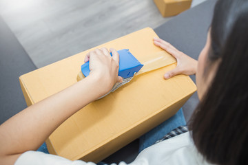Young asian woman taping up a cardboard box in home office SME e-commerce business, relocation and new small business concept, SME concept