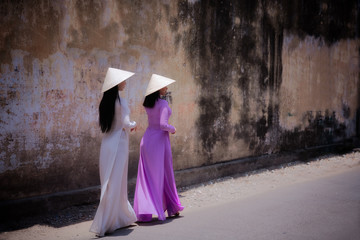 Young Vietnam woman wearing Ao Dai culture traditional walking on local street in Vietnam,vintage style,travel and relaxing concept.