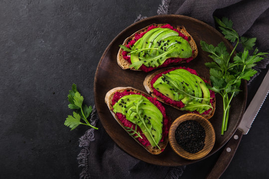 toasts with beetroot hummus and avocado on cutting board