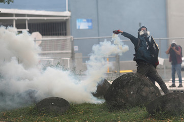 A demonstrator throws a tear gas canister during clashes with police at a May Day protest against austerity measures, in San Juan