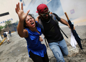 A woman affected by tear gas is assisted during a May Day protest against austerity measures, in San Juan, Puerto Rico