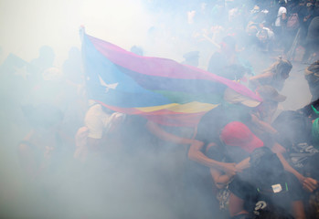 Demonstrators run from tear gas during a May Day protest against austerity measures, in San Juan