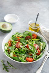 healthy vegan salad (tomatoes, avocado, cucumber, spinach and arugula) in white bowl