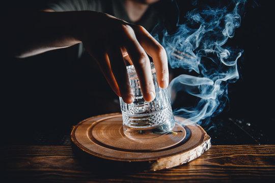 Barman prepares cocktail with smoke, raises a glass, pours alcohol. Dark background.