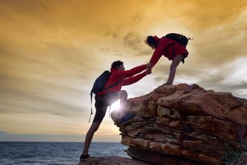 Young asian couple climbing up .