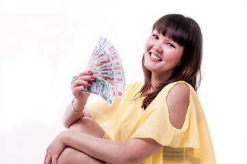 Happy brunette girl in yellow dress holding money