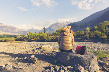 Young girl sitting on the rock relaxing see view in mountains with Cold weather, snow on hills.